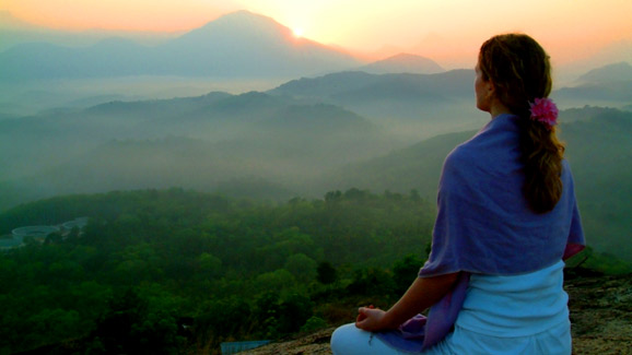 Woman Meditating Overlooking Mountains