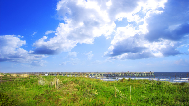 blue sky and clouds over sand dunes ocean and pier